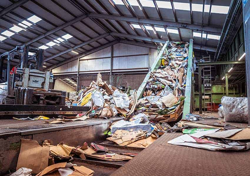 cardboard-waste-goes-into-the-cardboard-baler-forklift